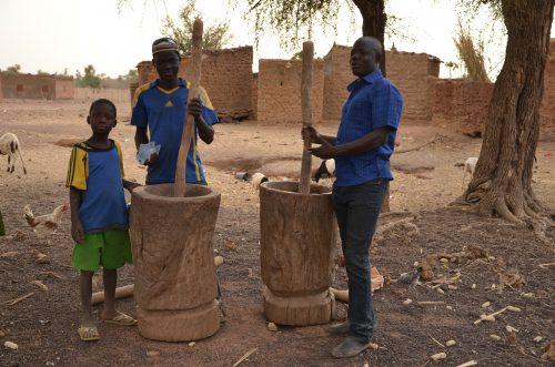 Burkinabés moulant des céréales
